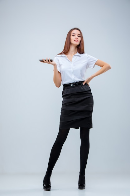 The young business woman on gray wall Free Photo