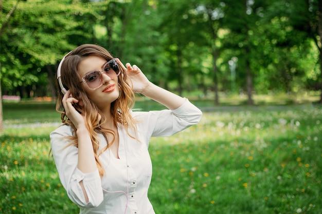 ヘッドフォンで若いビジネスウーマンは音楽を楽しんでいます Premium写真