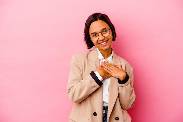 ピンクの壁に孤立した若いビジネスウーマンは、手のひらを胸に押し付けて、優しい表情をしています。愛の概念 Premium写真