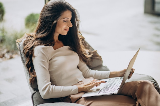 Giovane donna di affari che si siede in un cahir e che lavora al computer Foto Gratuite