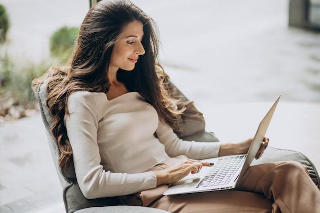 Молодая деловая женщина, сидящая в каыре и работающая на компьютере Бесплатные Фотографии