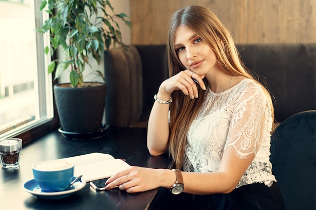 Young business woman sitting at the table in a coffee shop and making notes Premium Photo
