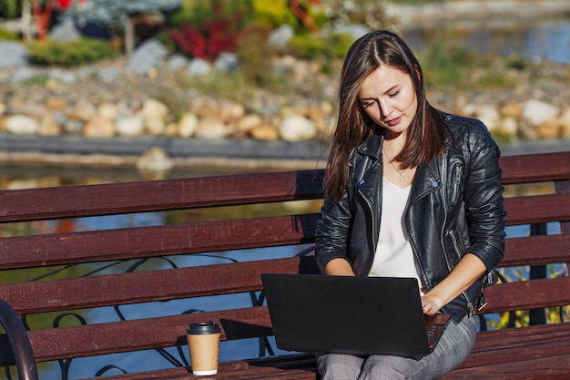 Young business woman sitting and working in park with laptop Premium Photo