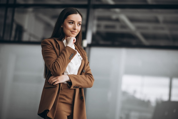 Young business woman standing in suit in office Free Photo