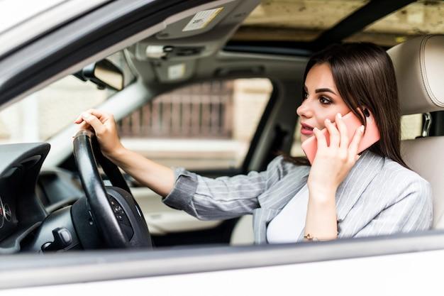 Young business woman utilizzando il suo telefono mentre si guida l'auto Foto Gratuite
