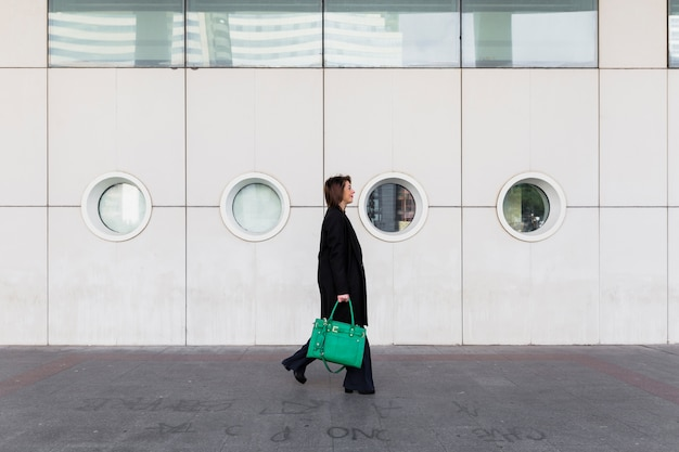Young business woman walking in street with green bag Free Photo