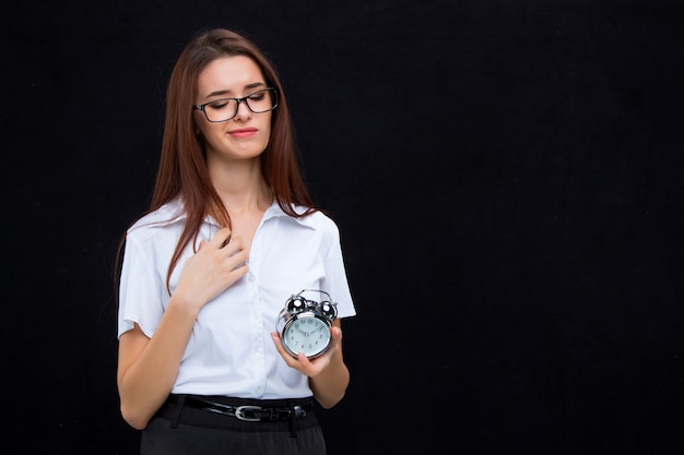 The young business woman with alarm clock on black wall Free Photo