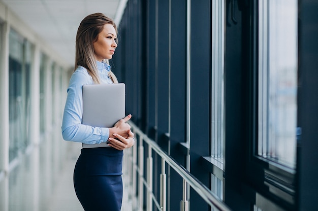 Young business woman with laptop standing in an office Free Photo