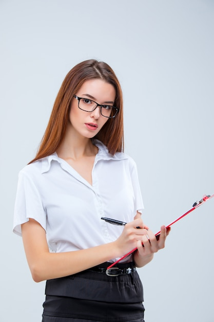 The young business woman with pen and tablet for notes on gray wall Free Photo