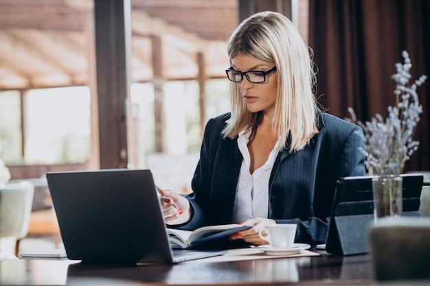 Giovane donna di affari che lavora al computer in un caffè Foto Gratuite