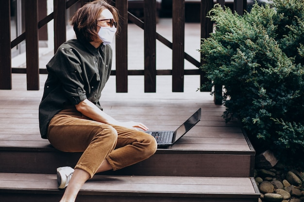 Young business woman working on computer from home in mask Free Photo
