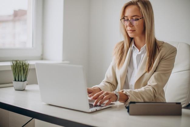사무실에있는 컴퓨터에서 작업하는 젊은 비즈니스 우먼 무료 사진