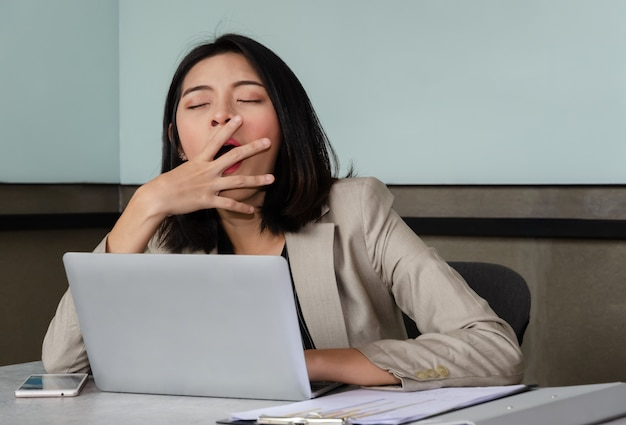 Premium Photo | Young business woman yawning at meeting office table in  front of laptop, covering her mouth out of courtesy. overwork and sleep  deprivation concept