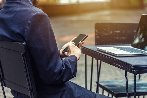Молодой бизнесмен использует смартфоны для связи с клиентами. Premium Фотографии