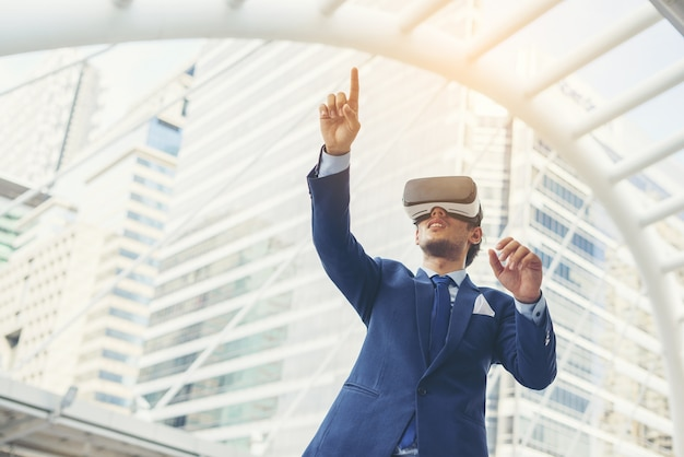 Young businessman in black suit wearing virtual reality goggles. Free Photo