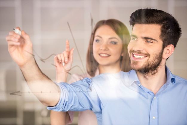 Young businessman and businesswoman drawing a graph. Premium Photo