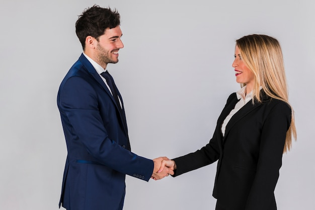 Young businessman and businesswoman shaking each other's hand against grey backdrop Free Photo