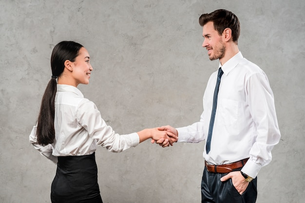 Young businessman and businesswoman shaking each other's hand against grey wall Free Photo