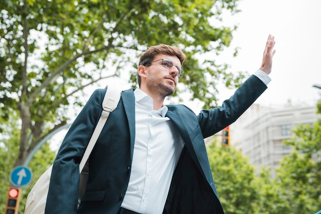 Young businessman carrying white backpack on his shoulder hitchhiking Free Photo