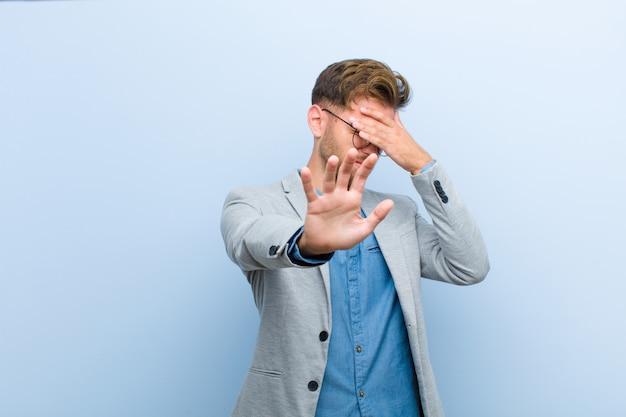 青年実業家の手で顔を覆って、他の手を前に置いてカメラを停止し、写真や写真を青に対して拒否 Premium写真
