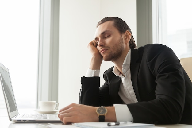 Young businessman dozed in front of laptop at work. Free Photo