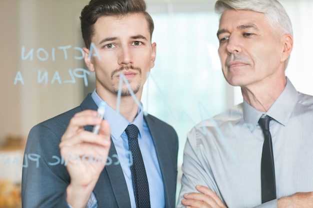 Young businessman drawing graph controlled by boss Free Photo