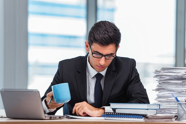 Premium Photo | Young businessman drinking tea in the office