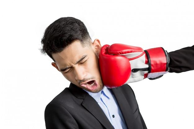 Молодой бизнесмен получая пунш в его лице с красными перчатками бокса. концепция деловой конкуренции Premium Фотографии