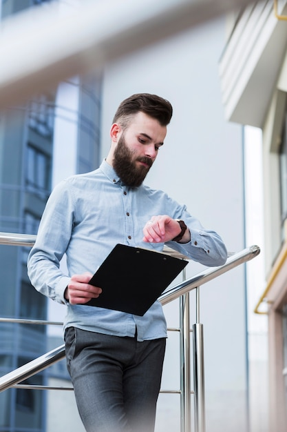 Young businessman holding clipboard in hand checking time Free Photo