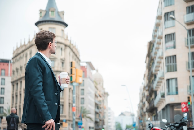 Young businessman holding coffee cup in hand looking at buildings in the city Free Photo
