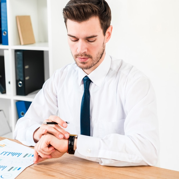 Young businessman holding pen in hand watching the time on wrist watch Free Photo