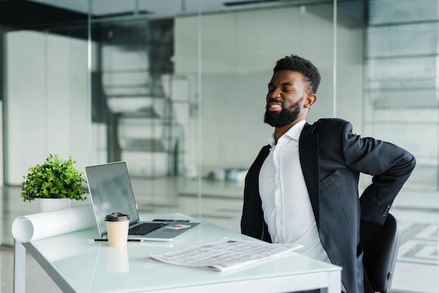 オフィスで背中の痛みに苦しんでいるデスクでオフィスの青年実業家 無料写真