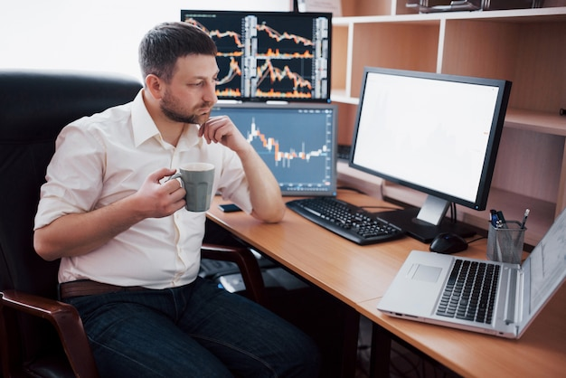 Young businessman is sitting in office at table, working on computer with many monitors,diagrams on monitor. stock broker analyzes binary options charts.hipster man drinking coffee,studying Free Photo