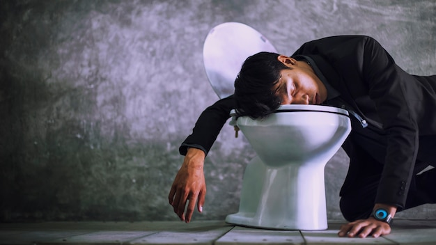 A young businessman is sleeping in the bathroom Premium Photo