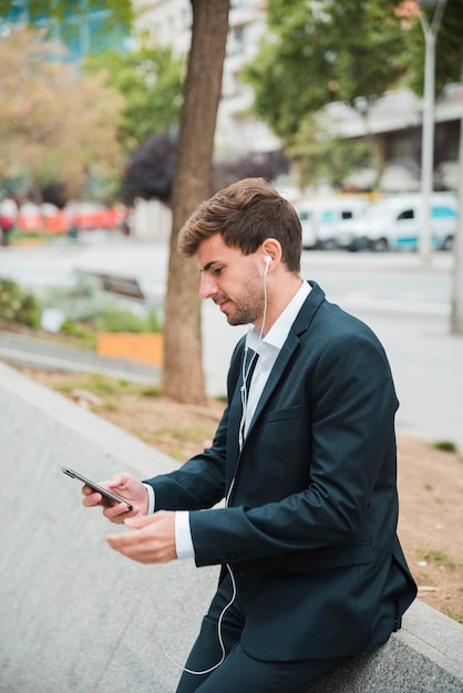 Young businessman leaning on street using mobile phone with earphone on his ears Free Photo