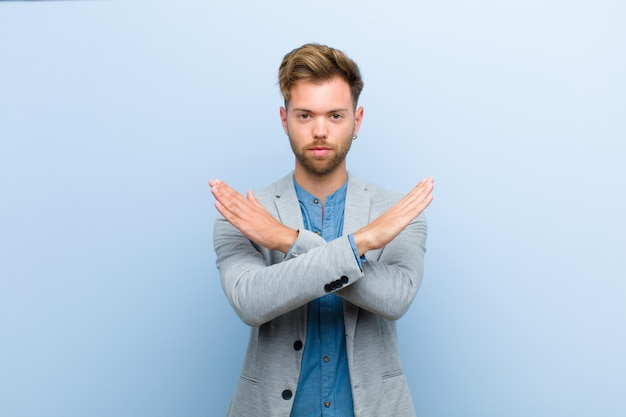 Young businessman looking annoyed and sick of your attitude, saying enough! hands crossed up front, telling you to stop against blue Premium Photo