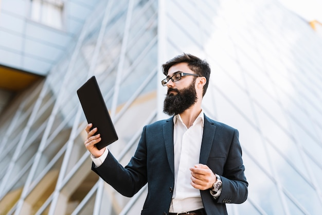 Young businessman looking at digital tablet standing in front of building Free Photo