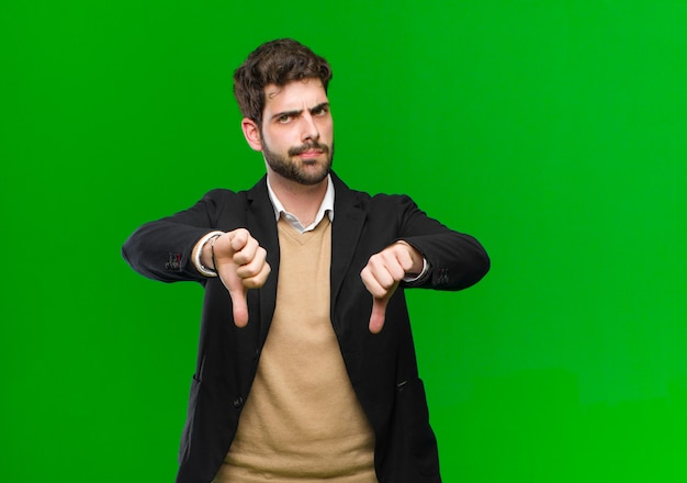 Young businessman looking sad, disappointed or angry, showing thumbs down in disagreement, feeling frustrated against green Premium Photo