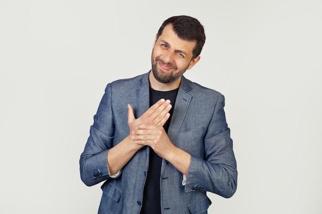 Молодой бизнесмен с бородой в куртке, страдает от боли в руках и пальцах, воспалении артрита. Premium Фотографии