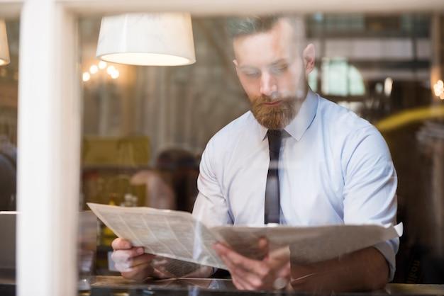 Молодой бизнесмен читает газету Бесплатные Фотографии