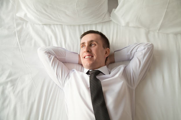 Young businessman relaxing in bed Free Photo