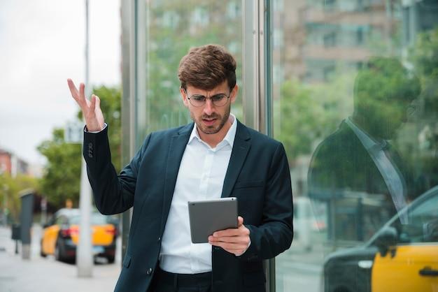デジタルタブレットを見ながら肩をすくめて青年実業家 無料写真