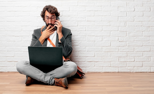 Young businessman sitting on the floor with a laptop Premium Photo