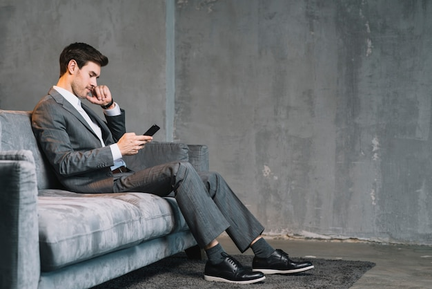Young businessman sitting on grey sofa using cellphone Free Photo