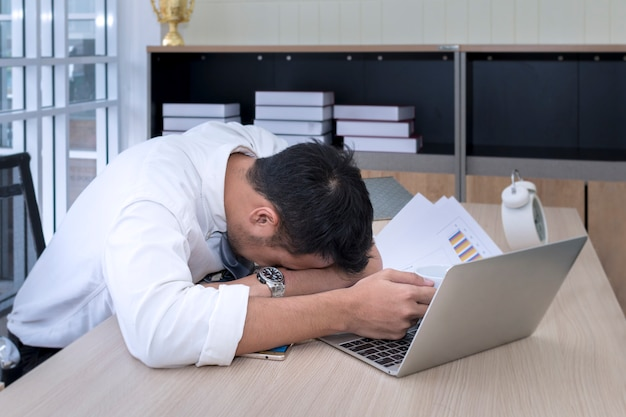Young businessman sleeping and overworked near laptop at office. Premium Photo