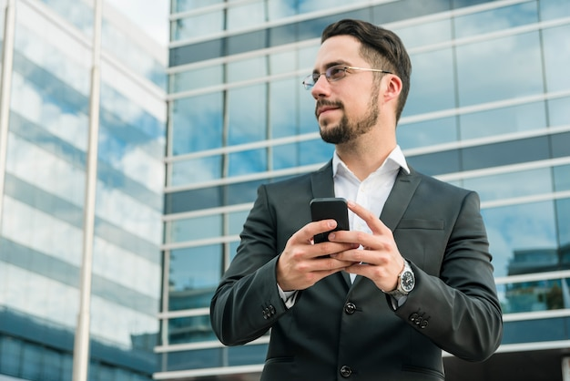 Young businessman standing in front of office building holding mobile phone Free Photo
