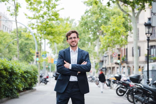 Young businessman standing on street with his arm crossed looking at camera Free Photo