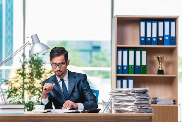 Young businessman in stress with lots of paperwork Premium Photo