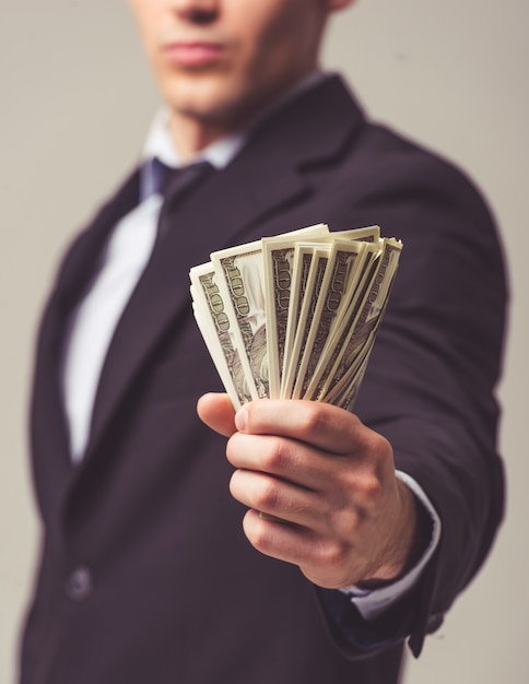 Young businessman in suit holding money Premium Photo