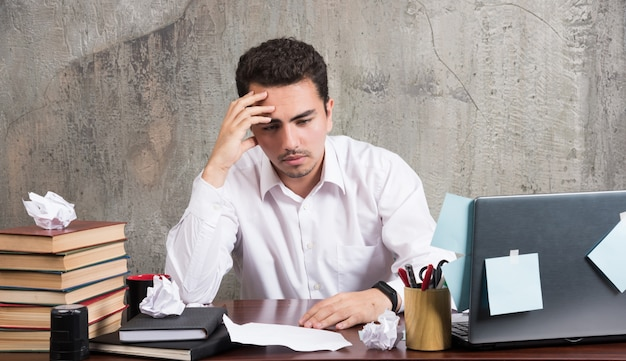 Giovane imprenditore pensando intensamente alla scrivania in ufficio. Foto Gratuite